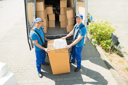 Photo for Two Happy Movers In Blue Uniform Loading Boxes In Truck - Royalty Free Image