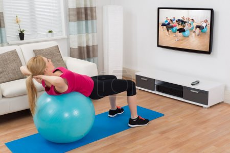 Woman Exercising With Fitness Ball While Watching Program