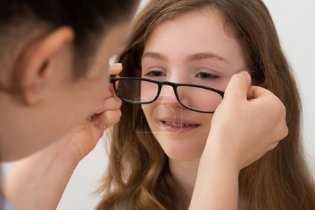 Optician Putting Eyeglasses On A Patient
