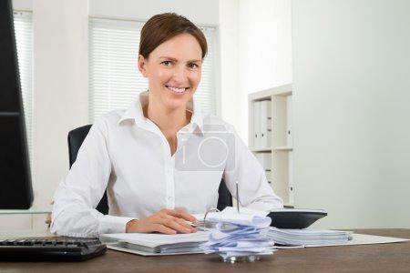 Businesswoman Calculating Bills