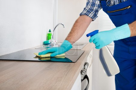 Photo for Close-up Of Worker Cleaning Electric Hob At The Countertop With Cloth - Royalty Free Image