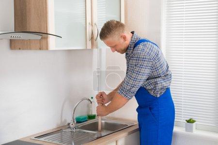 Plumber Using Plunger In Sink