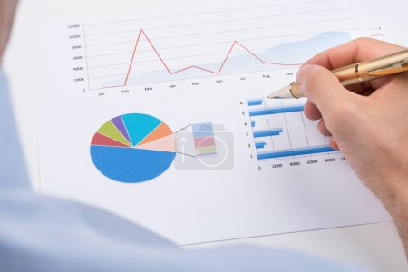Photo for Close-up Of Businessperson With Pen Analyzing Statistic Chart On Paper - Royalty Free Image
