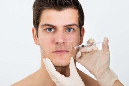 Hands Injecting Syringe On Man Face