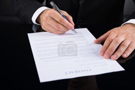Photo pour Gros plan de l'homme d'affaires signature contrat papier avec un stylo - image libre de droit