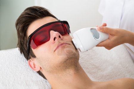 Photo for Young Man Receiving Laser Hair Removal Treatment At Beauty Center - Royalty Free Image
