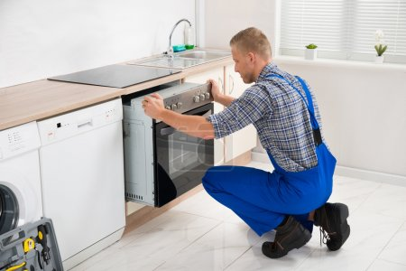Photo for Young Repairman In Overall Repairing Oven In Kitchen - Royalty Free Image