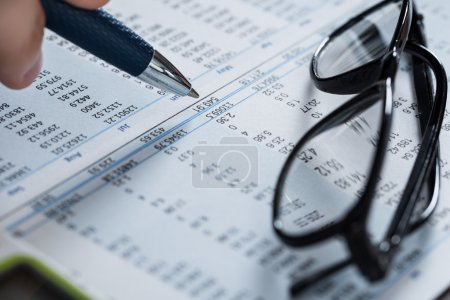 Person Hand With Pen And Glasses Over Financial Paper