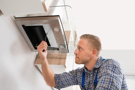Photo pour Cagoule de cuisine de réparation de travailleur masculin avec tournevis dans la cuisine - image libre de droit