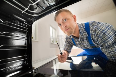 Photo for Young Repairman With Screwdriver Fixing Kitchen Oven - Royalty Free Image
