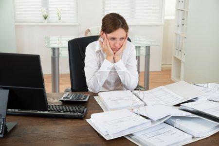Photo pour Malheureuse comptable féminine avec des dossiers de travail au bureau - image libre de droit