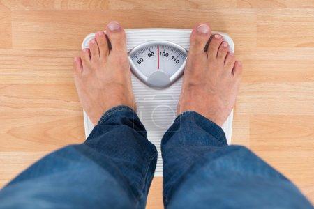 Photo pour Section basse de l'homme debout sur l'échelle de pesage - image libre de droit