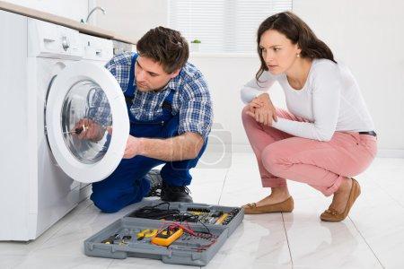 Repairman Repairing Washer In Front Of Woman