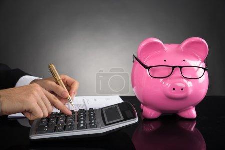 Photo pour Gros plan de femme d'affaires avec sa tirelire, calcul de l'impôt au bureau - image libre de droit