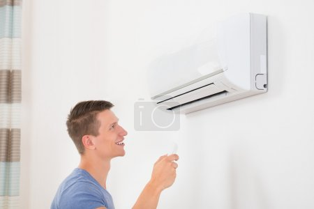 Man With Remote Control of  Air Conditioner