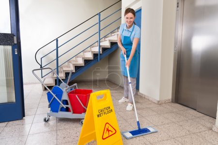 Photo for Young Happy Female Worker With Cleaning Equipment And Wet Floor Sign On Floor - Royalty Free Image