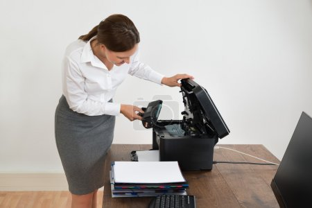 Businesswoman Putting Laser Toner Cartridge