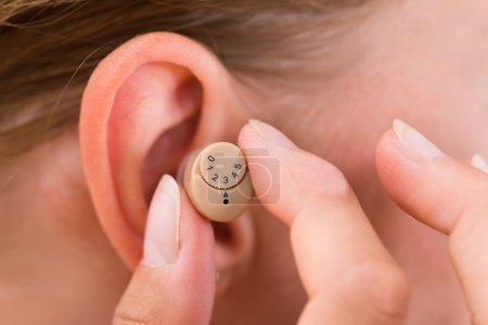 Hands Putting Hearing Aid In Ear