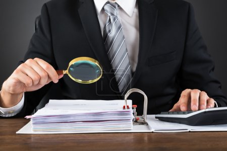 Close-up Of Businessman Inspecting Invoice With Ma...