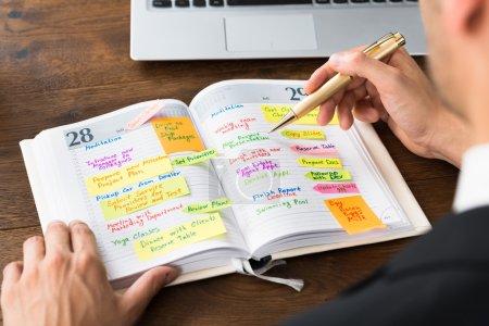 Photo pour Gros plan de la liste de lecture d'homme d'affaires de travail dans le journal - image libre de droit
