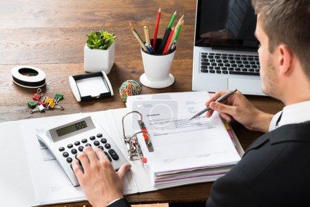 Businessman Calculating Receipt