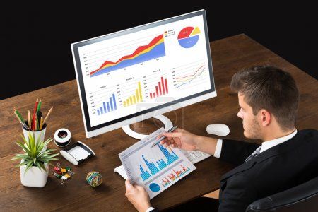 Photo for Young Businessman Analyzing Statistic Report At Desk - Royalty Free Image