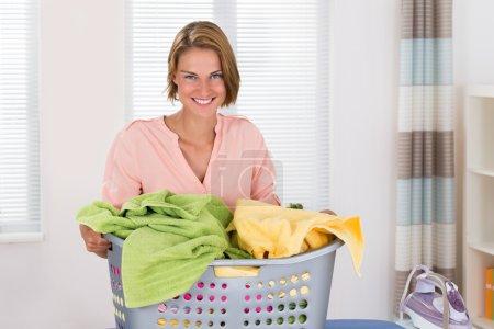 Photo pour Jeune femme heureuse avec panier de vêtements et fer à repasser - image libre de droit