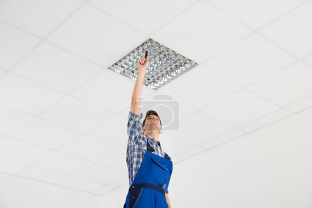 Electrician Installing Ceiling Light