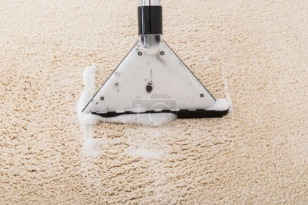 Photo for Close-up Of Vacuum Cleaner With Foam Over Wet Carpet - Royalty Free Image