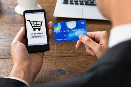 Photo pour Gros plan de l'homme d'affaires faisant du shopping en ligne avec son téléphone portable et sa carte de crédit - image libre de droit