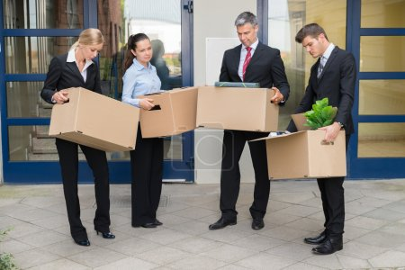 Unhappy Businesspeople With Cardboard Boxes Outside