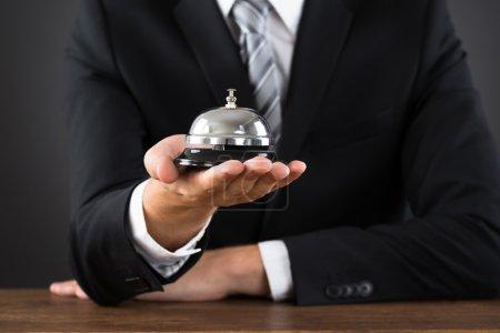Photo pour Gros plan sur le service de maintien des mains des gens d'affaires Bell au bureau - image libre de droit