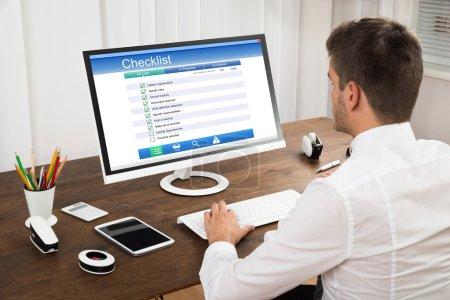 Photo pour Formulaire de liste de contrôle de remplissage de jeune homme d'affaires sur l'ordinateur au bureau en bois - image libre de droit
