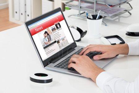 Photo pour Gros plan de Businessperson Vérification Nouvelles en ligne sur ordinateur portable au bureau - image libre de droit