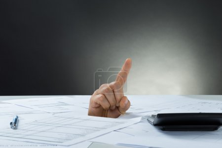 Businessman's Hand Emerging From Documents