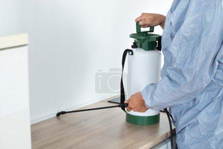 Exterminator Spraying Pesticide On Kitchen Counter
