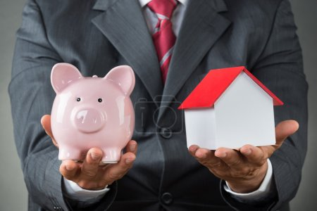 Holding Piggy Bank And House Model