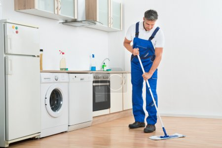 Worker Mopping Floor In Kitchen At Home