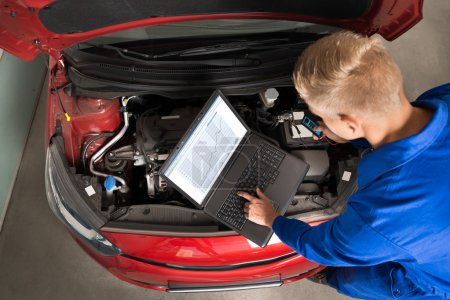 Photo for High Angle View Of Mechanic Using Laptop To Repair Car In Garage - Royalty Free Image