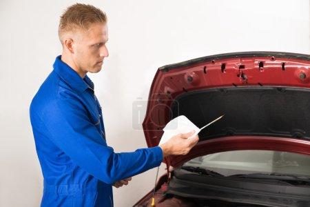 Photo pour Gros plan d'un mécanicien vérifiant le niveau d'huile dans le moteur de voiture - image libre de droit