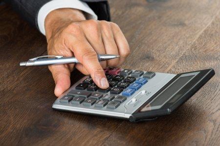 Photo pour Image recadrée d'un homme d'affaires utilisant une calculatrice sur un bureau en bois - image libre de droit