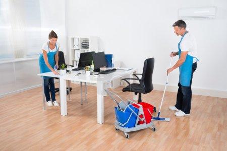 Photo pour Deux préposés au ménage avec nettoyage des appareils de nettoyage ensemble au bureau - image libre de droit