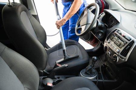 Photo pour Midsection de l'homme aspirateur siège d'auto avec aspirateur - image libre de droit