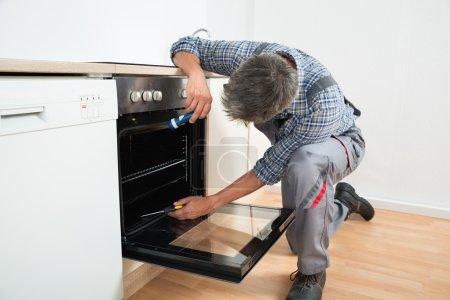 Repairman Examining Oven With Flashlight