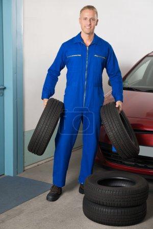 Photo pour Jeune mécanicien souriant tenant des pneus debout près de la voiture - image libre de droit