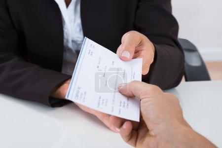 Photo pour Gros plan sur les mains d'un homme d'affaires qui remet un chèque à une autre personne au bureau - image libre de droit
