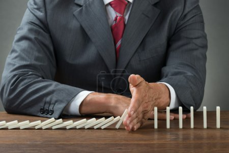 Businessman Stopping Dominoes Falling