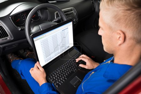 Mechanic Sitting In Car And Using Laptop