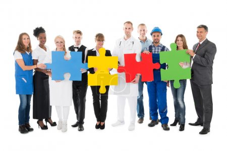 Photo for Portrait of confident people with various occupations holding jigsaw pieces while standing against white background - Royalty Free Image