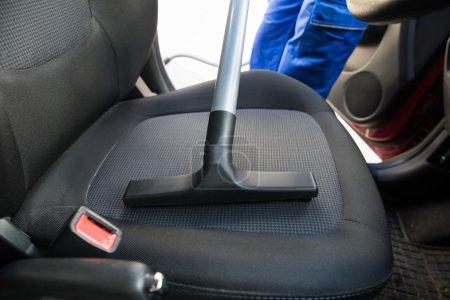 Photo pour Image recadrée de l'homme aspirant siège d'auto avec aspirateur - image libre de droit